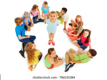 Nice looking little girl stand in the center of circle of kids smile and look up
