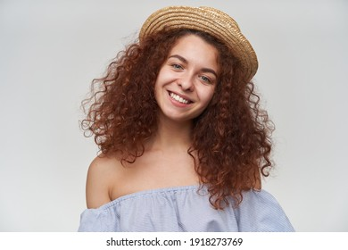 Nice looking woman, beautiful girl with curly ginger hair. Wearing striped off-shoulders blouse and hat. Tilt her head and smile. Watching at the camera, closeup, isolated over white background