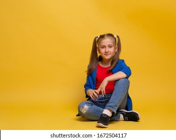 nice lovely cute attractive cheerful young girl sitting on the floor in jeans red t-shirt and blu jacket looking at you on yellow background