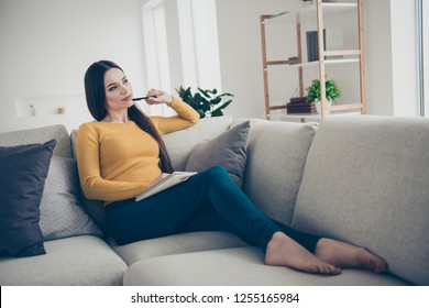 Nice lovely slim winsome attractive curious creative smart clever girl sitting on divan fantasizing writing commercial texts textbook in light interior room