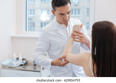 Nice male doctor holding his patients hand