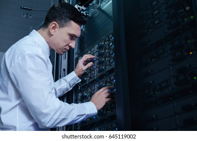 Nice male engineer checking the network server