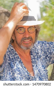 A nice man with a beard, a white hat, glasses and a blue shirt staring at the camera - Portrait