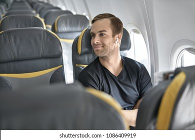 Nice man sits in the airplane next to the window on the background of the empty seats. He wears a black T-shirt and wireless headphones and looks ito the side with a smile. Closeup. Horizontal.