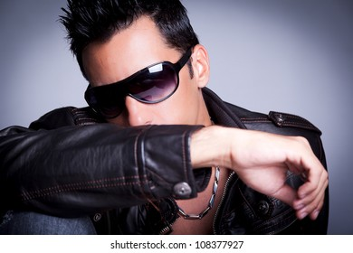 Nice man wearing a leather jacket and jeans and sunglasses, showing his chest since he is not using a shirt. The guy is on a sexy pose.