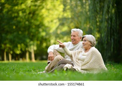 Nice mature couple sitting on green grass in summer park. Woman pointing with finger