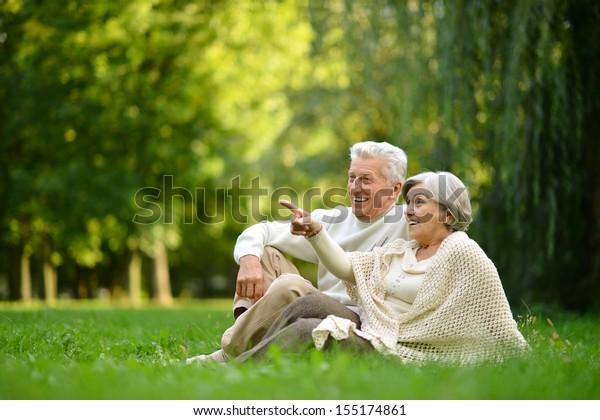 Schönes reifes Paar, das im Sommerpark auf grünem Gras sitzt. Weibchen mit Finger