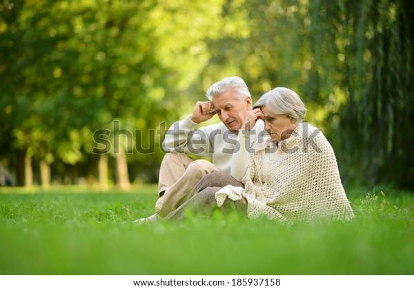 Nice mature couple sitting on green grass in summer park