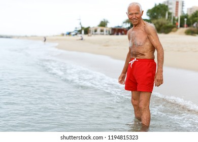 Nice mature man checks the water temperature on the beach