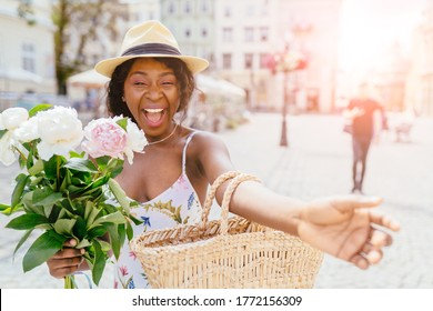 Nice to meet you. Charming nigerian gir in stylish hat holding bouquet of peonies, keeping smile on her face while want embracing you over old building, expressing energy in Europe. Sun glare effect.