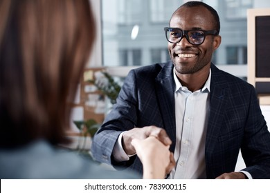 Nice to meet you. Portrait of cheerful young manager in glasses is sitting at table and having firm handshake with new female employee. He is expressing gladness while looking at woman