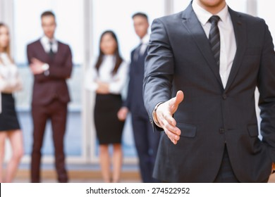 Nice to meet you.  Young business man standing in foreground extending hand for a handshake, his co-workers discussing business matters in the background