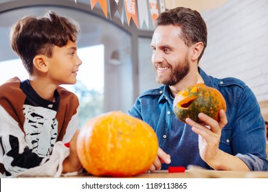 Nice memories. Bearded beaming father feeling memorable carving pumpkins with his son before Halloween celebration