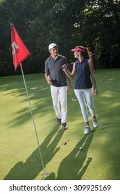 Nice middle aged couple playing golf during a sunny day. They both reach the green of the fifth hole and its red flag and are smiling at each other. They are wearing caps and sportswear outfits