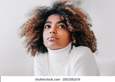 Nice model with perfect dark skin and trendy short brown kinky hair looking upwards against white studio background closeup