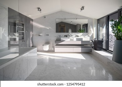 Nice modern bathroom with white and dark walls, large windows, triangular ceiling and tiled floor. There is white bath, gray stand with two sinks, wide mirror, toilet, towel rack, door, lamps.