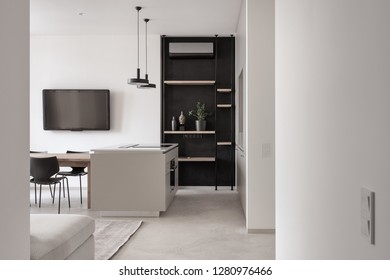 Nice modern kitchen with light walls and a gray floor with a carpet. There is a kitchen island with a cooking surface, lockers, shelves, hanging black lamps, dark TV, conditioner, table, chairs, sofa.