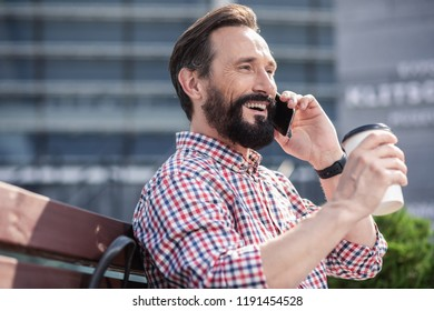 Nice morning. Cheerful handsome man talking on phone while drinking coffee