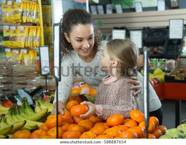 nice mother and daughter buying mandarins in shop