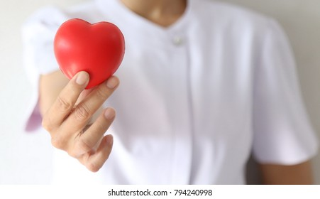 a nice nurse in white uniform hold a red heart with the finger on the valentine's day