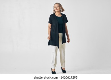 Nice old woman black jacket shoes full growth self-confidence pensioner gray background