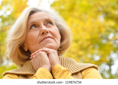nice older woman stands on a background of yellow autumn