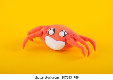Nice orange crab made of modelling clay laying on yellow background