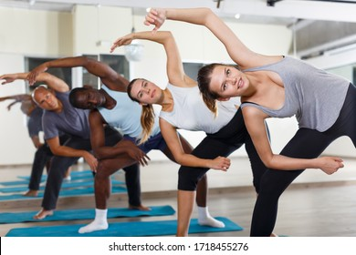 Nice people exercising during yoga class in modern fitness center