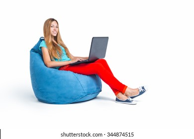 Nice photo of beautiful young woman isolated on white background. Woman smiling, using laptop and sitting on big cushioned frameless chair