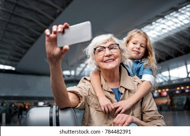 Nice photo. Portrait of cheerful aged charming grandmother is standing at airport lounge with her little granddaughter and looking at screen of mobile phone while taking selfie
