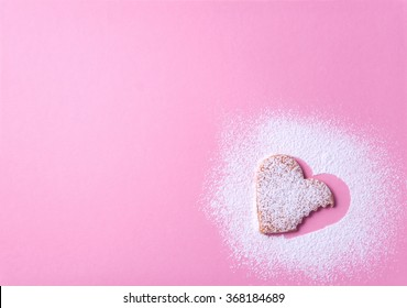 NIce picture of a beautiful heart shaped cookie with sugar icing on a pink paper background taken a bite from it