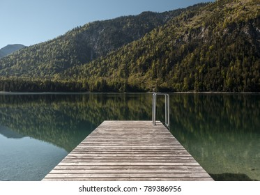 Nice pier in front of calm lake in summer.