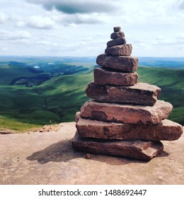 A nice pile of rocks with beautiful green rolling mountains in the background - shot at the top of Pen Y Fan in Wales.