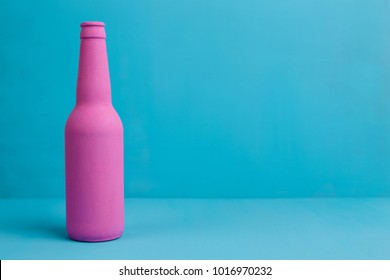 Nice pink beer bottle on blue background. Deceptive attraction of alcohol.  Alcoholism addiction, alcohol abuse and alcohol dependence concept. Copy space