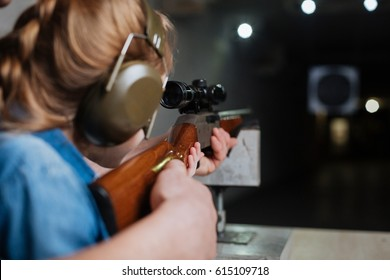 Nice pleasant girl developing her shooting skills