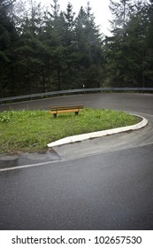 A nice point of view shot of a small wooden bench on grass in the middle of a winding rural road in the mountains.