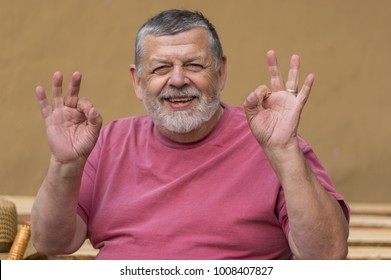 Nice portrait of bearded senior man being happy and showing that everything is ok