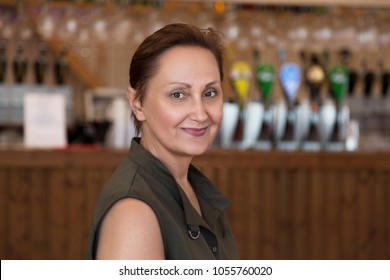 Nice portrait of a middle aged older woman in a pub. Professional headshot of 45 50 year old relaxed female wearing a sleeveless khaki top, looking at camera and smiling. Lifestyle shot.