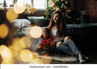 Nice portrait. Mother and daughter sits in holiday decorated room and holds gift box.