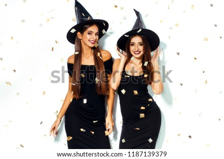 Nice Portrait Of Two Beautiful Young Woman In Black Witch Halloween Costumes  On Party Over White