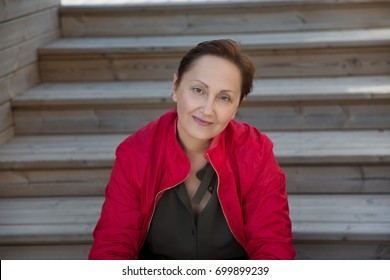 Nice portrait of a woman outdoors. Headshot of middle aged 40 50 year older female wearing red jacket. Blurred wooden background.