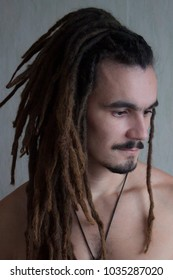 A nice portrait of a young man wearing long dreadlocks