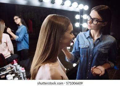 Nice positive makeup artist using face powder
