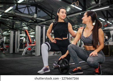 Nice and positive young asian woman stand on one knee and look at her friend. she smile and touch her shoulder. Young european woman sit and look too. She smiles.