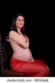 Nice pregnant woman sitting at studio on a black background