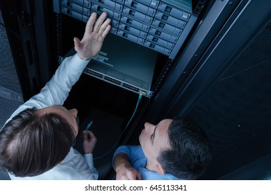 Nice professional technician pointing at the hard drives