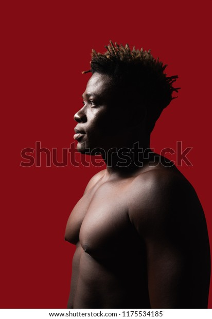 Nice profile. Side view portrait of naked strong guy posing at studio. He is looking away with serious expression