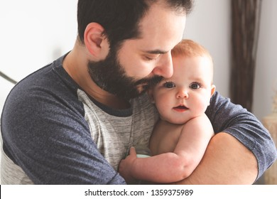 A Nice and protect father with baby on bed