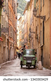 Nice, Provence Alpes Cote d'Azur / France - October 11 2014:  Retro delivery trike on a French side street lined with pastel stucco buildings, in a Mediterranean travel scene