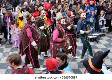 Nice, Provence, France - March 5, 2014: Colourful and happy carnival revellers enjoy a masked and uniformed band in the Nice Carnival procession